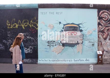 Couple walking passé Birgit Kinder's artwork de voiture Trabant éclatant à travers la paroi Cinquième mise à jour Banque D'Images