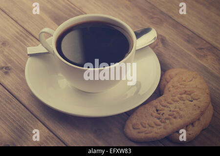 Tasse de café avec les cookies sur la vieille table en bois. Banque D'Images