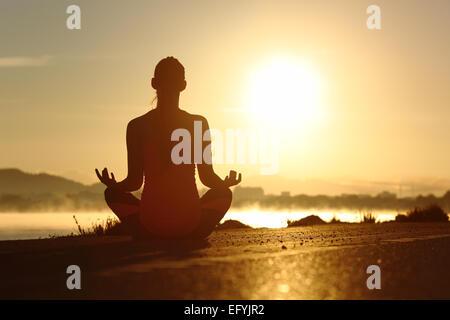 Silhouette d'une femme de remise en forme l'exercice de yoga méditation exercices avec le soleil en arrière-plan Banque D'Images