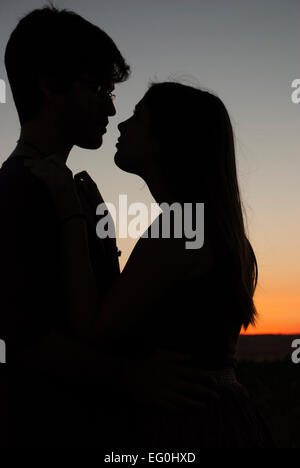 Silhouette de couple embrassant au coucher du soleil Banque D'Images