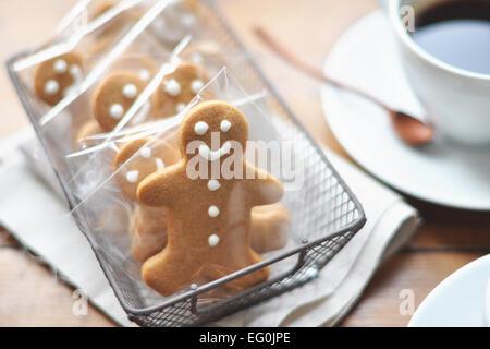 Gingerbread men in a row et du café sur la table Banque D'Images