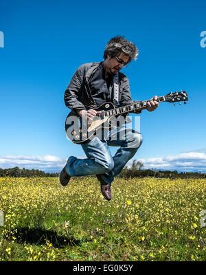Homme jouant de la guitare dans un champ Banque D'Images
