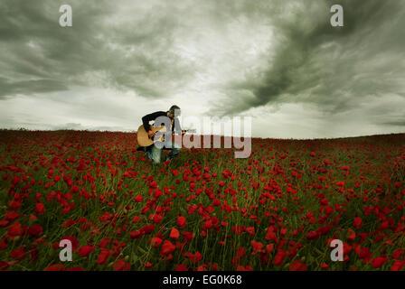 Homme jouant de la guitare dans champ de coquelicots Banque D'Images