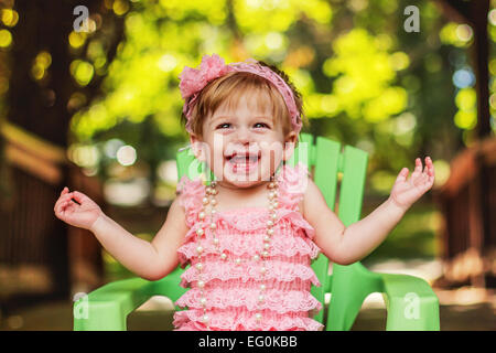 Happy girl in a party dress sitting in garden chair laughing Banque D'Images