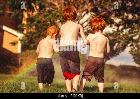 Trois jeunes frères jouant à aspersion d'eau