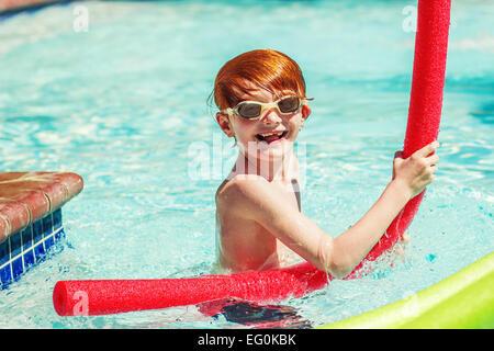 Jeune garçon (6-7) playing in swimming pool