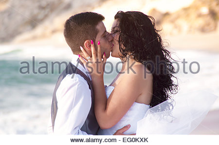 Groom kissing son épouse on beach Banque D'Images
