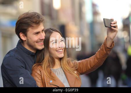 En couple avec une photo selfies smart phone dans la rue avec un arrière-plan flou Banque D'Images
