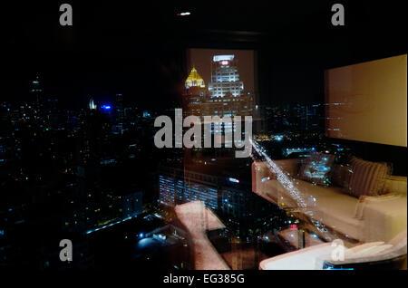 Vue nocturne des gratte-ciel de Bangkok à travers une fenêtre avec la réflexion de la chambre à l'hôtel Sofitel Banque D'Images