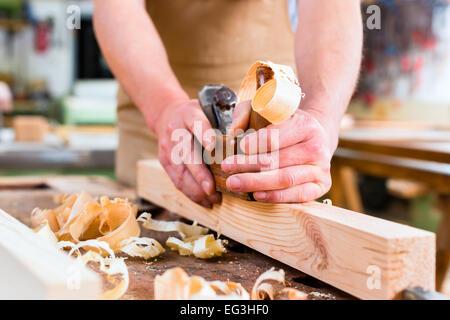 Menuisier travaillant avec un bois de charpente sur la pièce dans son atelier de menuiserie ou