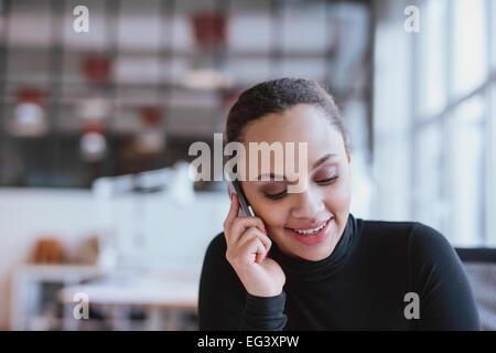 Libre de droit de jeune femme parlant au téléphone mobile. African American female model using cell phone au travail. Banque D'Images