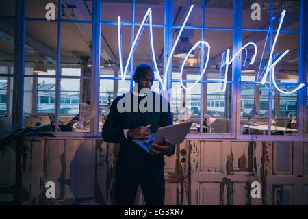 African young man standing in office à l'aide d'un ordinateur portable. Bureau exécutif des affaires dans de grands Banque D'Images