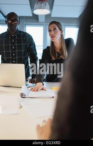 Businesswoman travaille sur de nouvelles idées. Jeune femme montrant nouveau projet d'entreprise à des collègues Banque D'Images