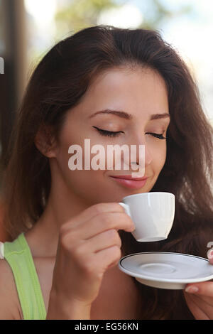 Belle femme de boire du café avec le visage et yeux clos appréciant. Closeup portrait