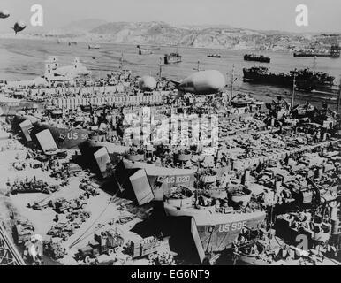 Alliés à l'invasion des navires dans un port du sud de l'Italie d'être chargé avec les véhicules et les fournitures. Banque D'Images