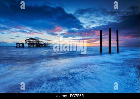 Les restes en décomposition de Brighton West Pier au coucher du soleil avec la marée. Banque D'Images