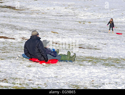 Man and boy sur l'ensemble de la Luge Luge descente sur snowy hillside Caldbeck fells, Lake District, Cumbria, Angleterre, Banque D'Images