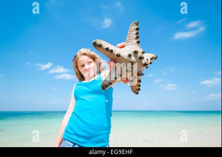 Fille sur la plage holding starfish, Okinawa, Japon Banque D'Images