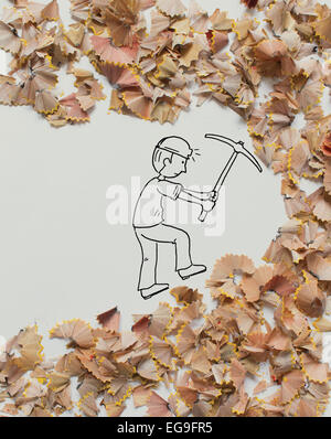 Mineur conceptuel creuser dans des copeaux de crayon Banque D'Images