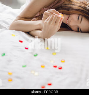 Femme souriante couchée sur un lit mangeant des bonbons