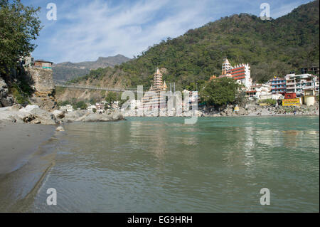 Vue de la plage avec les temples et les montagnes de Rishikesh avec Lakshman Jhula bridge traversant le Gange. Banque D'Images