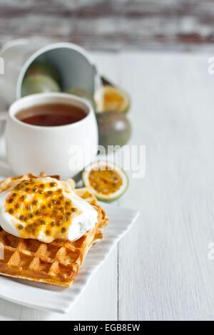 Gaufres belges faites maison avec de la crème et de la pâte de fruit de la passion. Focus sélectif. Copyspace arrière Banque D'Images