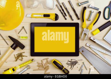 Tablette numérique et divers outils de menuiserie et ébénisterie sur table Atelier Pin Banque D'Images