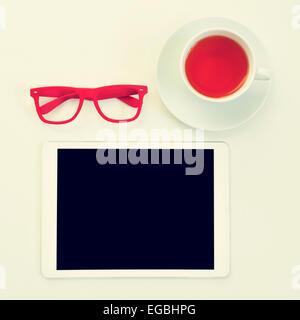 Capture d'un grand angle d'une table avec une paire de lunettes cerclées de rouge en plastique, un ordinateur tablette Banque D'Images