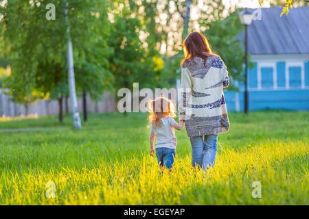 Mère et fille marcher à sunny park Banque D'Images
