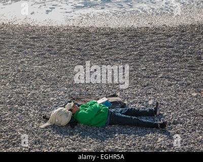 Un homme prenant une sieste sur la plage de Nice, en France, dans le soleil de décembre. Banque D'Images