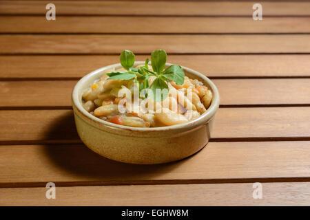 Ragoût de haricots espagnol épicé avec des légumes dans un bol en terre cuite. Fabada Asturiana. Banque D'Images
