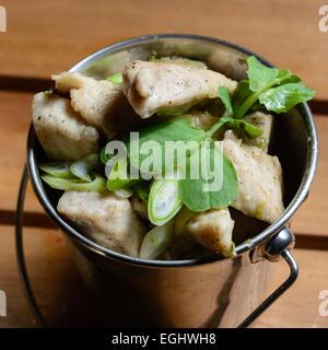 Tapas de poulet légèrement épicé avec des oignons de printemps. Servi dans un bol en acier de forme de godet Banque D'Images