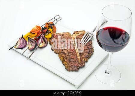 T bone steak sur une plaque blanche avec des légumes grillés et verre de vin rouge shot on white Banque D'Images