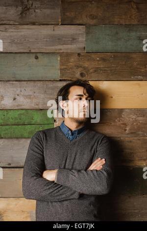 Beau jeune homme d'affaires appuyée contre un mur en bois, les bras croisés à la route. Banque D'Images