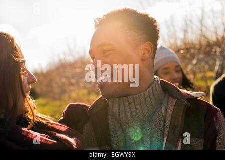 Un groupe de trois amis à l'extérieur sur une marche d'hiver. Banque D'Images