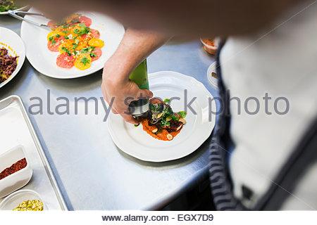 Chef de la nourriture avec placage en sauce cuisine commerciale Banque D'Images