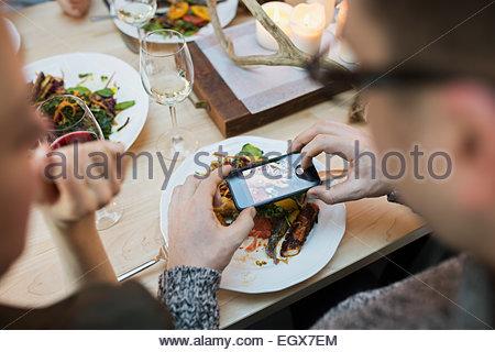 Man photographing assiette de nourriture au restaurant table Banque D'Images