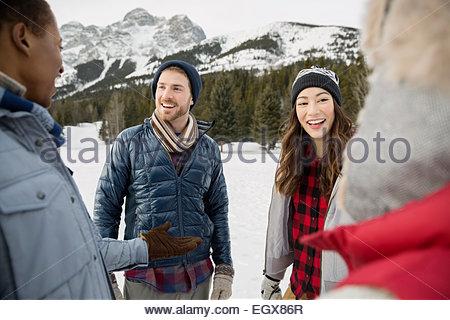 Friends talking in snowy field montagnes ci-dessous Banque D'Images
