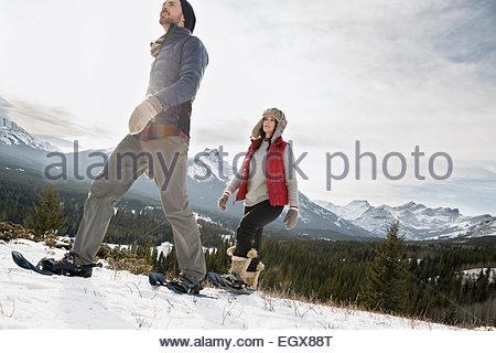 Couple snowshoeing ci-dessous montagnes enneigées Banque D'Images