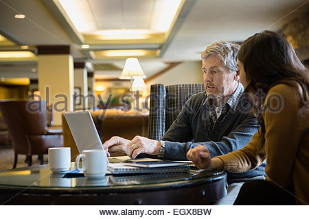 Businessman and businesswoman working at laptop in lobby Banque D'Images