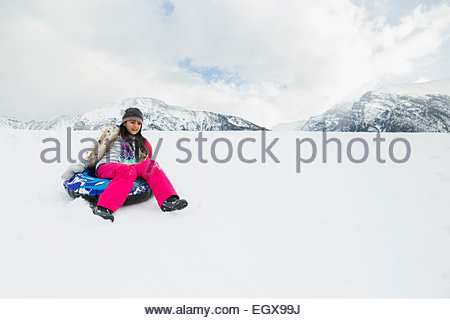 Girl riding tube intérieur bas snowy hill Banque D'Images