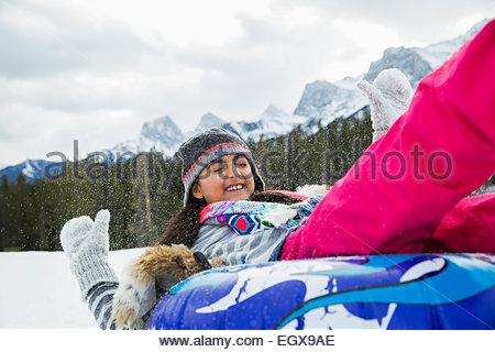 Fille jouant sur le tube intérieur dans la neige Banque D'Images