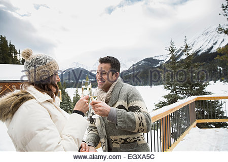 Couple toasting with champagne glasses on pont enneigé Banque D'Images