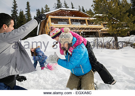 En famille ludique snowball fight in snowy field Banque D'Images