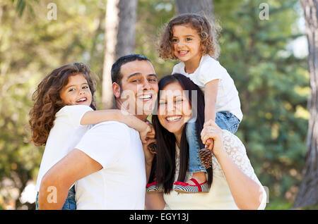 Heureux parents hispaniques donnant aux enfants piggyback Banque D'Images