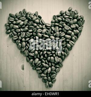 Un tas de grains de café torréfiés formant un cœur, sur une table en bois , en noir et blanc Banque D'Images