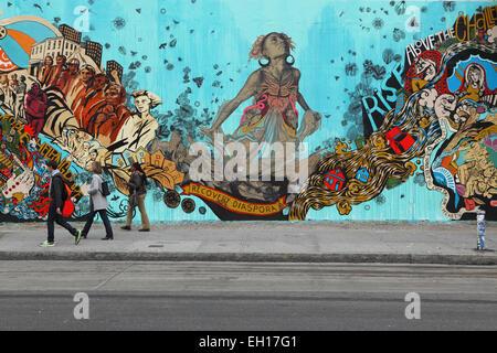 Les New Yorkers marchent pour passer devant une fresque colorée installée par Swoon sur le mur mural Bowery mural sur Houston Street dans le Bas