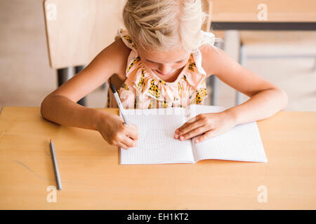 Girl writing in book at desk in classroom Banque D'Images