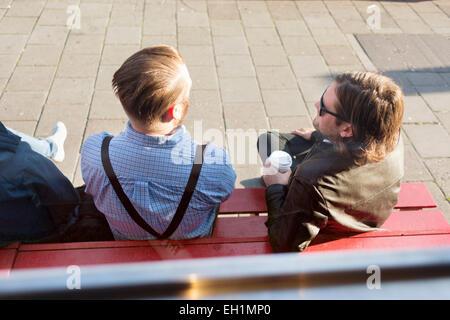 Portrait d'hommes assis sur un banc à l'extérieur Banque D'Images