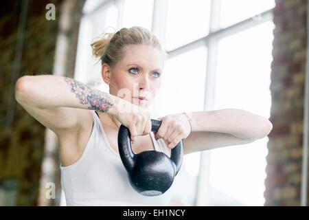 Jeune femme déterminée dans kittlebell s'entraîner avec le club de santé Banque D'Images